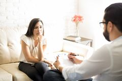 Pensive female patient taking advice from psychiatrist. Pensive young hispanic female patient listening advice from male psychiatrist during therapy session Stock Image