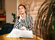 Pensive female student with book at the table looking up Stock Images