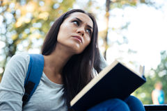 Pensive female student looking away outdoors Royalty Free Stock Photos