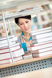 Pensive female student looks at the books Stock Photo