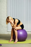 Pensive fit woman sitting on the fitball Stock Images