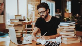 Pensive Freelance Text Writer Working at Desk. Pensive Handsome Hardworking Freelance Screenwriter Scenarist Sits Near Big Stacks of Books Writing Article stock images