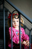 Pensive girl. Preschool age girl pensively sitting on stairs looking at camera through banister Stock Image