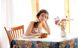 Pensive girl with book sitting at table indoor Royalty Free Stock Photo