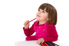 Pensive girl with colored pencils. Three years old girl, drawing with coloring pencils. Smiling and thinking about what she will draw. Shot in the studio Royalty Free Stock Photo