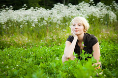 Pensive Girl in a field of flowers Stock Images