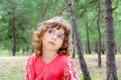 Pensive girl in forest thinking gesture Stock Photo