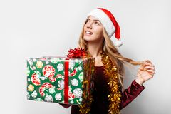 Pensive girl in a hat of Santa Claus, in her hands - Christmas g royalty free stock photo