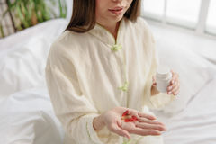 Pensive girl holding drug and glass of water Royalty Free Stock Images