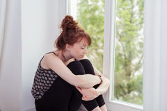 Pensive Girl Hugging her Knees at the Window Stock Image
