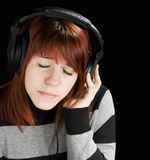 Pensive girl listening to music. Beautiful redhead girl listening to music on headphones. Studio shot royalty free stock photos