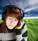Pensive girl listening to music. Beautiful redhead girl listening to music on headphones. Studio shot stock image