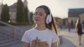 Pensive girl listens to music and dreams. 4K. Pensive girl listens to music and dreams stock video