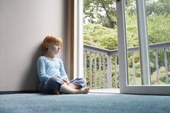 Pensive Girl Looking Through Balcony stock photography