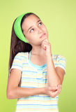 Pensive girl looking up. On a green bakcground Royalty Free Stock Photography