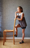 Pensive girl near the chair Stock Photography