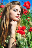 Pensive girl in poppy field Stock Images