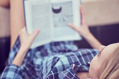 Pensive girl reading book. Young cute woman studying at home, lying on couch, copy space royalty free stock photo
