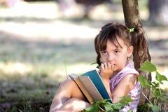 Pensive girl reading a book Stock Photos