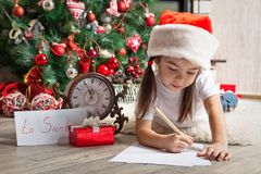 Pensive girl in Santa hat writes letter to Santa. Little girl in Santa hat writes letter to Santa Claus near christmas tree Stock Photo