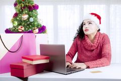 Pensive girl shopping online with a laptop Royalty Free Stock Images