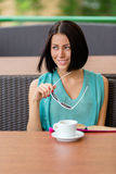 Pensive girl sits at the cafe with cup of tea Stock Photography