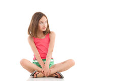 Pensive girl sitting with legs crossed Stock Image