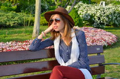 Pensive girl sitting on a park bench Royalty Free Stock Photos