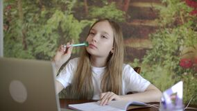 Pensive girl student solving problem at homework. Girl student doing schoolwork at home schooling. Distance school