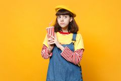 Pensive girl teenager in french beret, denim sundress holding plastic cup of cola or soda isolated on yellow wall. Background in studio. People sincere emotions stock image
