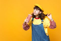 Pensive girl teenager in french beret, denim sundress holding plastic cup of cola or soda isolated on yellow wall. Background in studio. People sincere emotions royalty free stock images