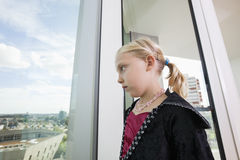 Pensive girl in vampire costume looking out through window at home Stock Images