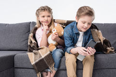 Pensive girl watching tv while brother looking at remote control Royalty Free Stock Images