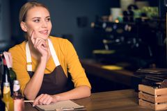 Pensive girl writing document at table. Portrait of thoughtful female barista dreaming while standing at counter and noting on paper. Muse concept Royalty Free Stock Photo