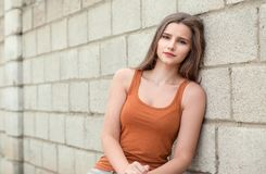 pensive girle looking at you sadly on cement color bricks background stock photography