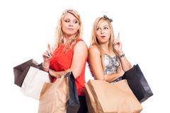 Pensive girls shopping and pointing up Stock Photography