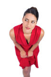 Pensive gorgeous brunette in red dress posing Royalty Free Stock Photography