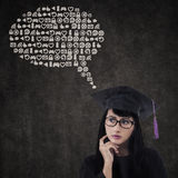 Pensive graduate with abstract cloud Stock Photo