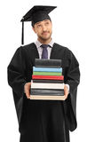 Pensive graduate student holding a stack of books Royalty Free Stock Image