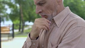Pensive grandfather sitting in garden, planning pension savings, making choice stock video footage