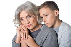 Pensive grandmother and grandson. Portrait of pensive grandmother and grandson isolated on white background Royalty Free Stock Image