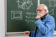 Pensive grey hair professor standing at blackboard with piece. Of chalk royalty free stock photo