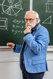 Pensive grey hair professor standing at blackboard with piece. Of chalk stock images