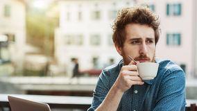 Pensive guy at the bar. Pensive young man having a coffee at the bar and looking away, city buildings on background Royalty Free Stock Images
