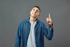 Pensive guy dressed in in white t-shirt and a jeans shirt points finger up on the gray background in the studio royalty free stock image