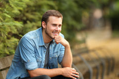 Pensive guy looking away in a park Stock Photography