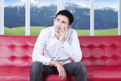 Pensive guy sitting on couch at home Stock Photography