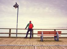 Pensive guy in trekking suit on a wooden pier above sea stock image