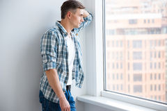 Pensive handsome man standing near the window Stock Image
