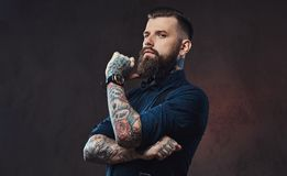 Pensive handsome old-fashioned hipster in a blue shirt and suspenders, standing with hand on chin in a studio. Royalty Free Stock Photography